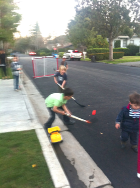 Here's an impromptu street hockey game my oldest son and some neighborhood friends organized in the parking lane in front of our street. This is far more likely to happen here than at a faraway park.