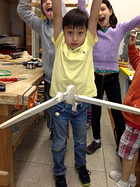 Marco holds the bird he made by thin fishing lines, like a marionette.  He made this at an after school program called Young Builders, but now that I've made the workshop in our garage, I plan to transfer his woodworking activities to there.