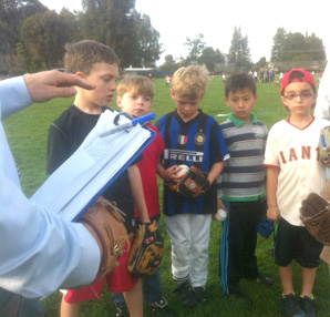 Marco, second from right, listens with teammates to instructions from their baseball coach, at left.