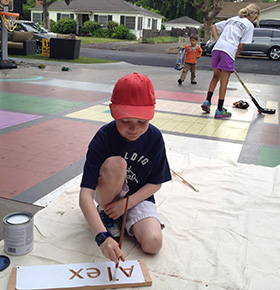 Alex paints his sign as kids play street hockey in the background.