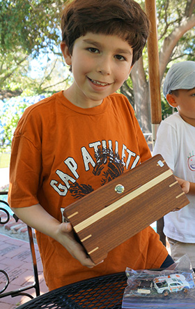 A boy carries a Quest Box for his teammates as they try to discover the one place where they can open it.