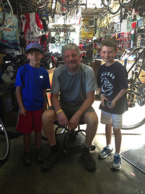 Rainier Zaechelein (center), the owner of Menlo Velo, our neighborhood bike shop, poses with two members of a Huntopoly team.  He gave them a slice of life in a bike shop from his point of view.