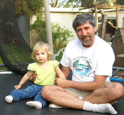 N Street co-founder Kevin Wolf and a young neighbor named April on a trampoline in the N Street communal back yard