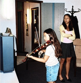 Amy Chua looks on as daughter Lulu plays violin in a hotel room, with the sheet music taped to a TV.  photo: Chua family