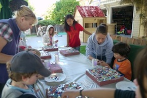 The kids are making mosaic 'stepping stones.'