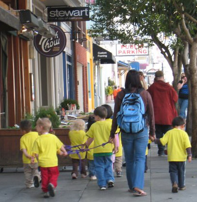 Kids on leashes in San Francisco.  Wouldn't they have more fun in a no-name small town in the Midwest?