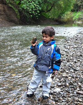 There's Nico, about to throw a rock in the creek.