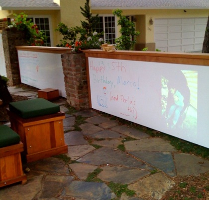 That image on the right side of the whiteboard of my front yard is projected from inside that picnic bench on the left. We'll project photos, videos, etc, and play music from this front yard media center.
